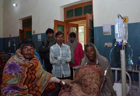 Homens são atendidos após consumirem bebida falsificada em Saharanpur, no norte da Índia