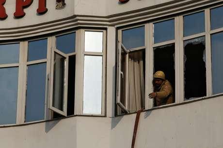 Bombeiro trabalha em janela de hotel que pegou fogo em Nova Délhi