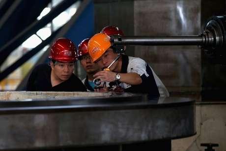 Operários chineses examinam equipamento de mineração em Shenyang; país é referência em reuso de rejeitos de mineração
