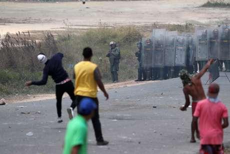 Manifestantes atiram pedras em direção às forças militares venezuelanas