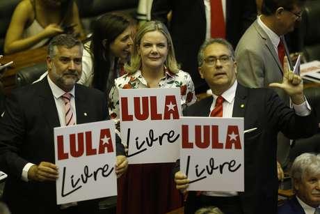 """E/D: os deputados federais Paulo Pimenta (PT-RS), Gleisi Hoffmann (PT- PR), presidente nacional do PT; e Carlos Zarattini (PT-SP) exibem cartazes pedindo """"Lula Livre"""" durante a cerimônia de posse na 56ª legislatura da Câmara dos Deputados"""