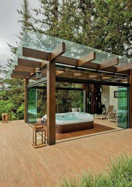 28. Para proteger sua banheira de hidromassagem, você pode cobrir o pergolado de madeira com uma placa de vidro