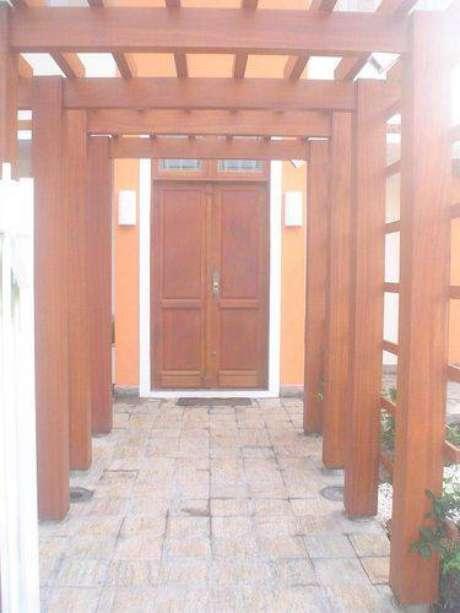 12. Pergolado de madeira na entrada da casa fica muito bonito