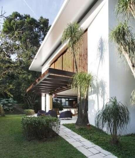 92. Casa moderna com pergolado de madeira e móveis embaixo – Foto: Gisele Taranto
