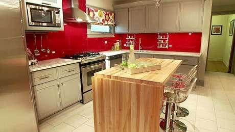 58- Utilizar o vermelho e detalhes de madeira na cozinha garante um ambiente moderno e confortável