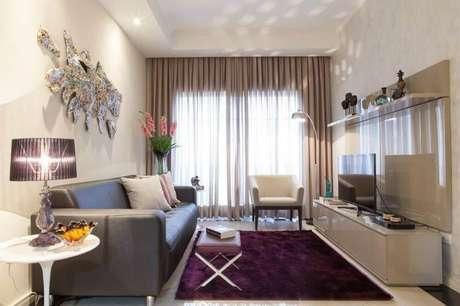 62- O tapete roxo garante um ambiente mais confortável para a sala em tons neutros
