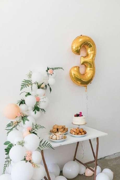 45. Delicada decoração para mesversário com arranjo de balões e folhagens – Foto: Sou Mãe