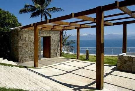 75. Estrutura com pergolado de madeira e parede de pedra – Foto: Enrico Benedetti