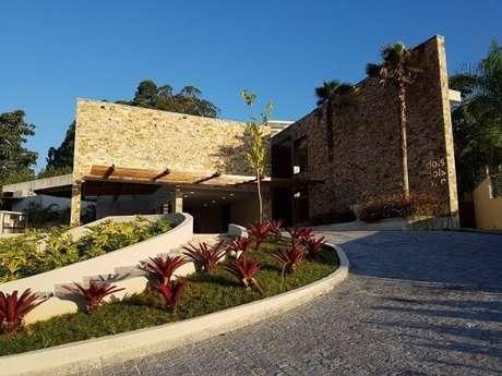 95. Fachada de casa moderna com revestimento de pedra e pergolado de madeira – Foto: C2HA Arquitetos