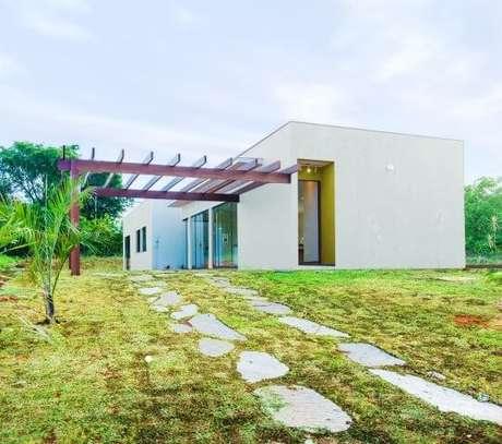 81. Fachada de casa moderna com pergolado de madeira e caminho de pedras – Foto: Mateus Castilho