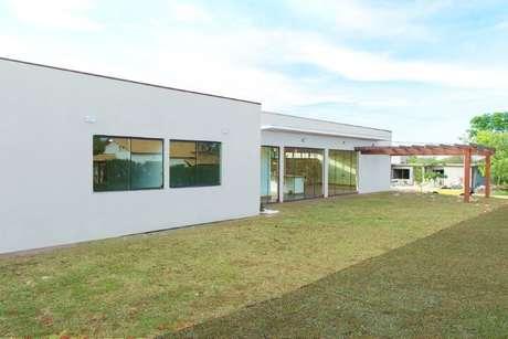 32. Fachada lateral de casa térrea moderna com pergolado de madeira. Projeto de Mateus Castilho