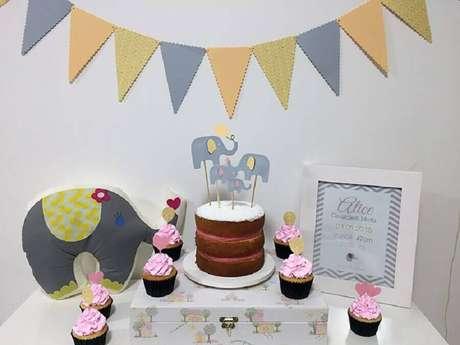 56. Mesversário simples decorado com elefantinho e varal de bandeirinhas – Foto: iBabysite