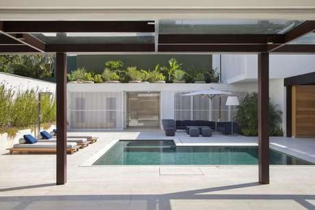 99. Pergolado de madeira com teto para casa moderna com piscina – Foto: Gisele Taranto