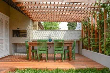 84. Decoração com pergolado de madeira combinando com piso e mesa de varanda com jardim vertical – Foto: Haus Best