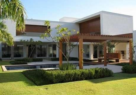 102. Casa moderna decorada com amplo jardim e pergolado de madeira na área externa – Foto: Roberto Migotto