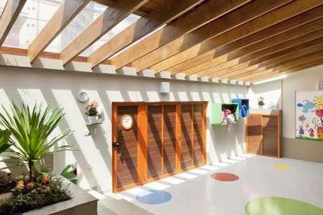 40. Playground com pergolado de madeira para entrada de luz natural. Projeto de Adelle Porto