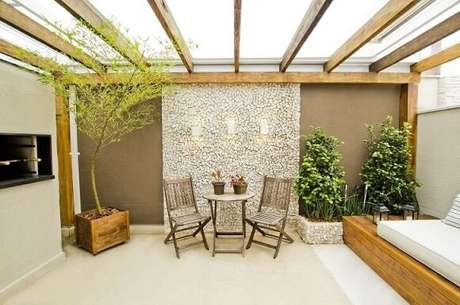 53. Terraço decorado em tons neutros com pergolado de madeira com churrasqueira – Foto: Schaelly Campos