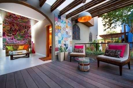36. Varanda com decoração colorida e pergolado de madeira e luminária. suspensa Projeto de DM Arquitetura