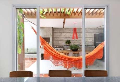 62. Decoração para varanda com pergolado de madeira e rede laranja – Foto: Antonio Armando de Araujo