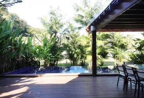35. Varanda gourmet com deck e pergolado de madeira perto da piscina. Projeto de Rawi Arquitetura
