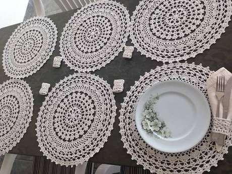15. O sousplat de crochê claro ganha destaque em tampos de mesa mais escuros.