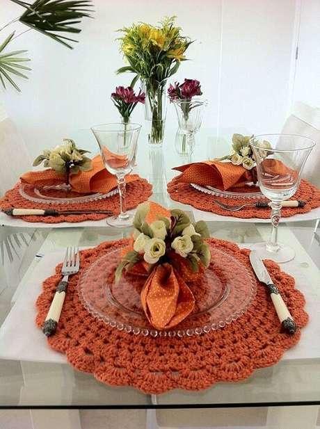 27. Os elementos ao redor do sousplat de crochê devem ser dispostos em harmonia para deixar a mesa mais bela.
