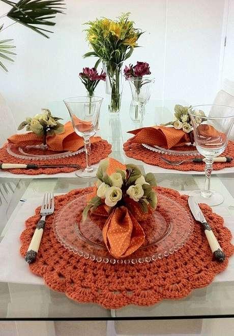 54- A decoração de mesa com sousplat de crochê laranja é complementada pelos guardanapos no mesmo tom e anéis de flores. Fonte: Pinterest