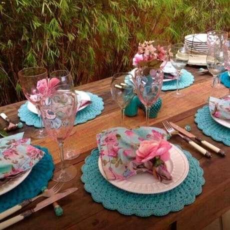 48- A decoração da mesa foi realizada com sousplat de crochê azul, taças na cor rosa, pratos brancos e guardanapos azuis estampados de rosa. Fonte: Blog da Tetê