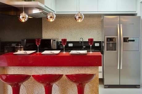 29. Decoração em tons de vermelho para cozinha planejada com armário aéreo branco – Foto: Aquiles Nícolas Kílaris