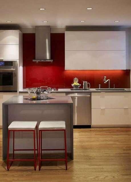7. Decoração moderna para cozinha vermelha com piso de madeira e ilha cinza – Foto: Pinosy