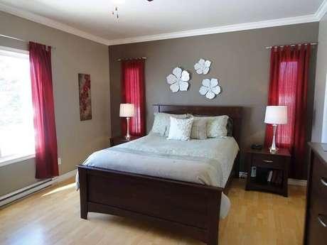 65. Tons de vermelho para decoração de quarto cinza com cama de criado mudo de madeira escura – Foto: Unsizdk