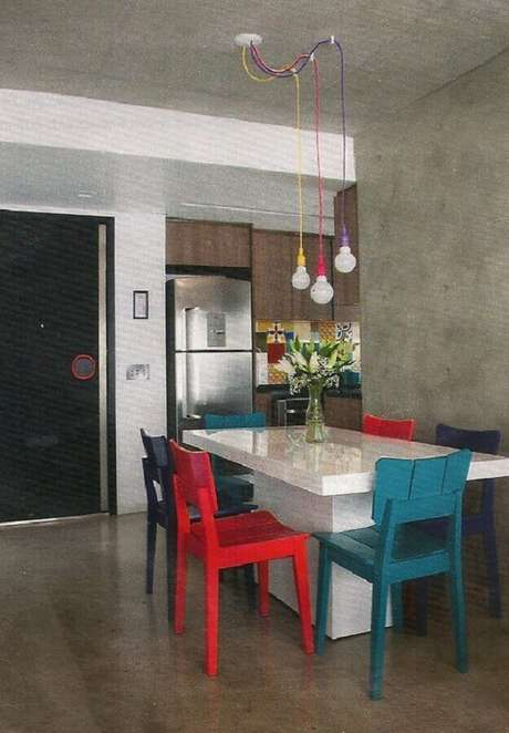 67. Decoração para sala de jantar com cadeiras vermelhas e azuis e pendentes coloridos sobre a mesa branca – Foto: Pinosy