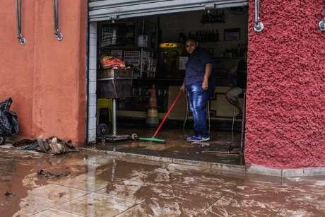 Homem limpa sujeira levada pela enchente no bairro do Cambuci, em São Paulo
