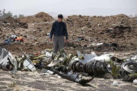 Homem caminha em meio aos destroços do avião da Ethiopian Airlines