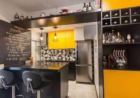 27. Decoração de cozinha preta e amarela com pendente e banquetas