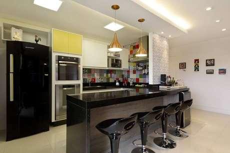 26. Cozinha americana com banquetas pretas reguláveis e pendentes dourados
