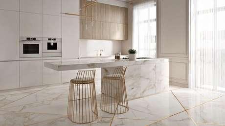 69. Cozinha sofisticada decorada com armários brancos planejados, pendente minimalistas e banquetas para cozinha douradas – Foto: Pinterest