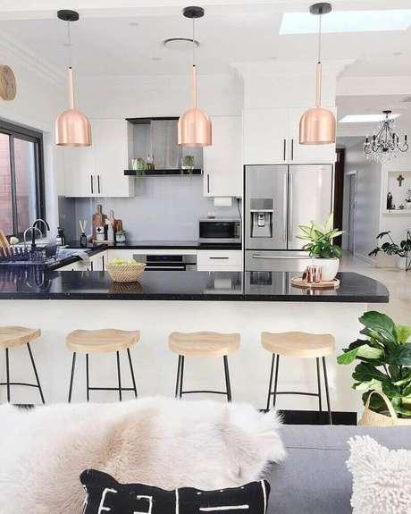 74. Decoração com pendentes rosé e banquetas para cozinha com assento de madeira – Foto: Pinterest