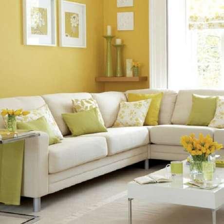 11- Na decoração de sala simples e barata as almofadas e objetos são amarelos e verdes para combinar com a parede. Fonte: Doce Obra