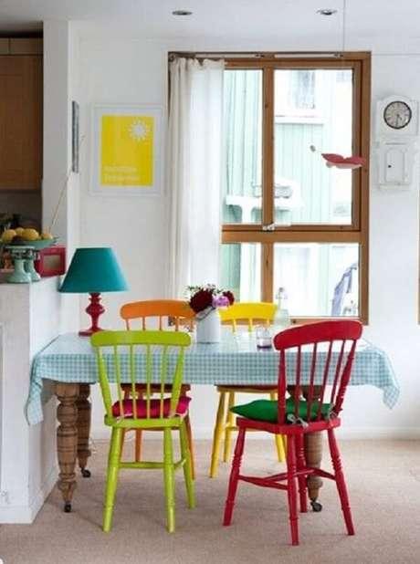 31- A decoração de sala simples e barata de jantar tem mesa em madeira natural e cadeiras coloridas. Fonte: Pinterest