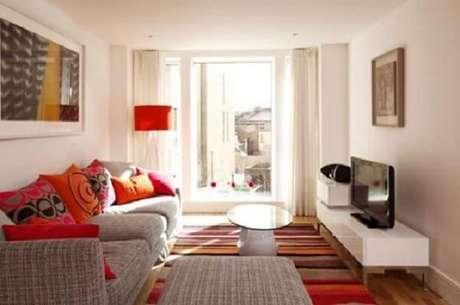 12- A decoração de sala simples e barata tem almofadas, tapete e abajur em tons de vermelho. Fonte: Mulher Portuguesa