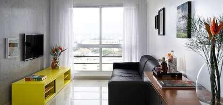 20- Na decoração de sala simples e barata cinza e preta, o rack amarelo se destaca. Fonte: Pruzak