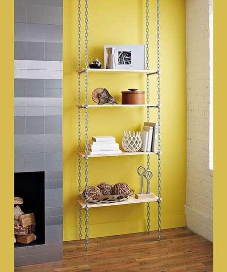27- A decoração de sala simples e barata tem estante feita com correntes e tábuas no cantinho do ambiente. Fonte: Cerâmica Burguina
