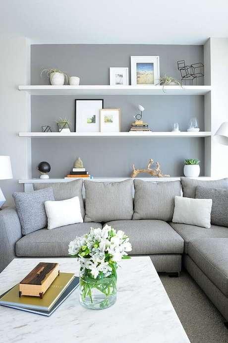 39- Na decoração de sala simples e barata, a parede cinza combina com o sofá. Fonte: Cerâmica Santo Antônio