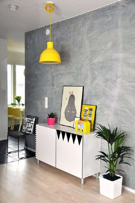 19- Na decoração de sala simples e barata, a parede de cimento aparente contrasta com os acessórios amarelos. Fonte: Dcore Você