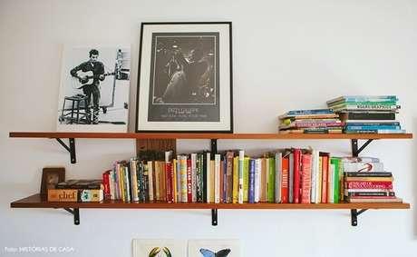 41 – A decoração de sala simples e barata tem prateleira com braçadeiras na cor preta. Fonte: Tua Casa