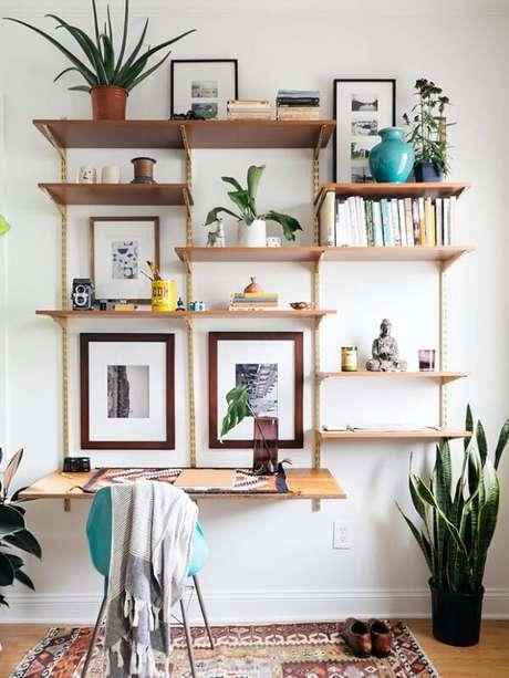 60- Na decoração de sala simples e barata, a estante com trilhos tem a função de escrivaninha. Fonte: Revista Glamour
