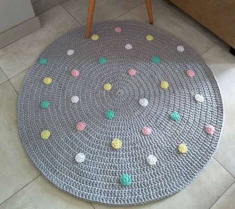 97. O tapete de crochê cinza com fuxicos coloridos é perfeito para decoração de quarto infantil – Foto: Pinosy