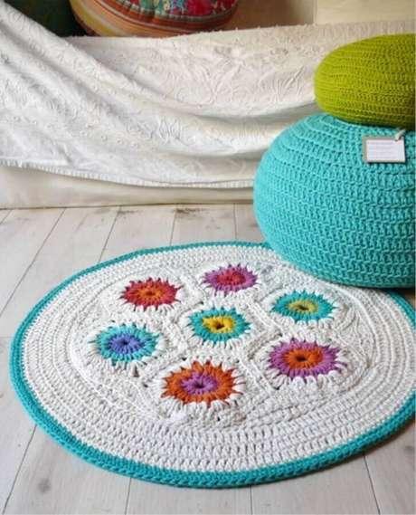 99. Modelo simples de tapete de crochê com flores coloridas e acabamento em azul na lateral – Foto: Etsy