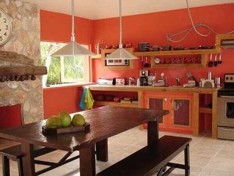 c8d522c6e5e2c 19- A cozinha em estilo rústico tem a parede pintada na cor salmão  alaranjada.